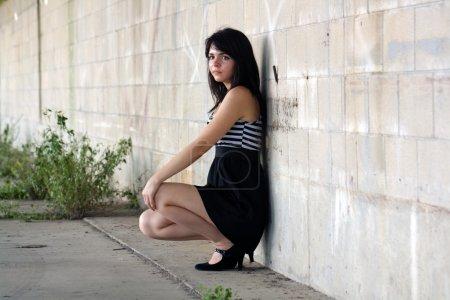 Photo pour Une belle jeune brune squats et se penche contre un mur de bloc, regardant hors caméra légèrement vers le cadre gauche avec une expression faciale sérieuse . - image libre de droit