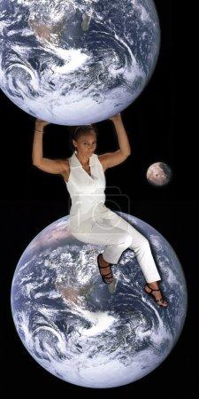 Photo pour Une belle femme noire mature se trouve sur la terre, tout en maintenant une autre terre au-dessus d'elle, avec une lune en arrière-plan. Cette photo est disponible sans la terre une - image libre de droit