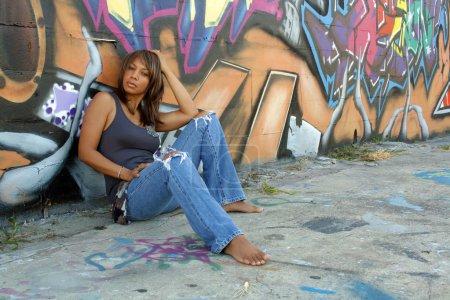 Photo pour Une belle femme noire mature, portant un jean en lambeaux, s'assoit devant un mur d'art graffiti . - image libre de droit
