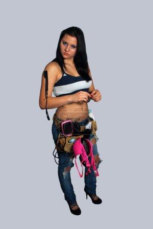 Photo pour Une jolie jeune brune porte une ceinture à outils remplie d'attirail féminin. Isolé sur un fond gris neutre . - image libre de droit