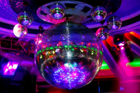 Photo for Mirrored disco ball hanging from the ceiling and puts colored sparks - Royalty Free Image