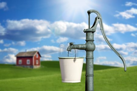 Photo for Water pump and a red cottage house - Royalty Free Image