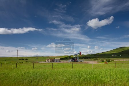 Beautiful landscape with green grass, blue sky and pumpjack. Pho