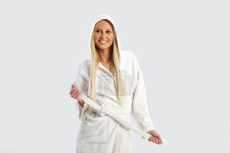 Photo pour Atrractive jeune fille blonde dans un peignoir blanc - image libre de droit