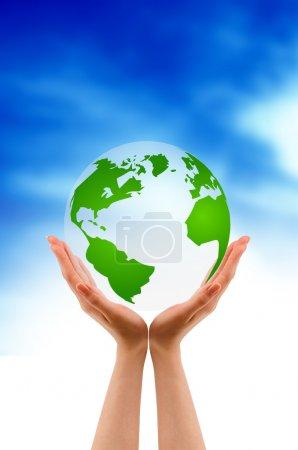 Photo pour Mains tenant un globe sur fond de nuage . - image libre de droit