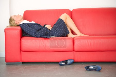 Exhausted businesswoman lying on the couch