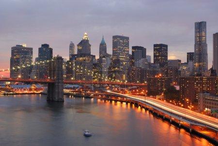 Photo pour Skyline de manhattan et brooklyn bridge avec mettant soleil derrière elle. - image libre de droit
