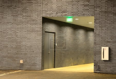 A hallway with grey brick and an exit sign....