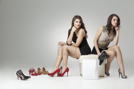 Two glamorous women trying high heels