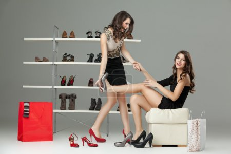 Photo for Two young women trying on high heels - Royalty Free Image