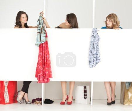 Photo pour Jeunes femmes essayant vêtements magasin garde-robe - image libre de droit