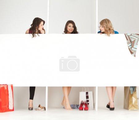 Photo pour Jeunes femmes essaient des vêtements catalogue armoire - image libre de droit