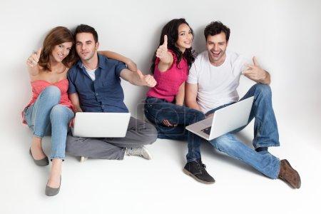 Photo pour Jeune groupe heureux amis hoding aprooving ordinateurs portables - image libre de droit
