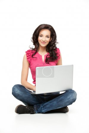 Photo for Young casual woman sitting down smiling holding laptop - Royalty Free Image