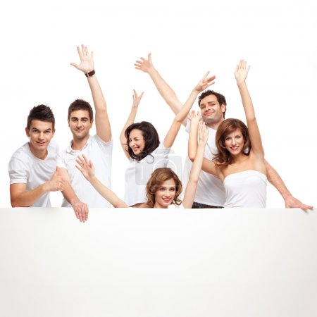 Photo for Group of smiling friends excited over a white banner - Royalty Free Image