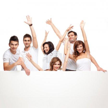 Foto de Grupo de amigos sonriendo emocionados sobre una bandera blanca - Imagen libre de derechos
