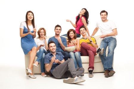 Foto de Amigos sentados en el sofá riéndose de película de comedia - Imagen libre de derechos