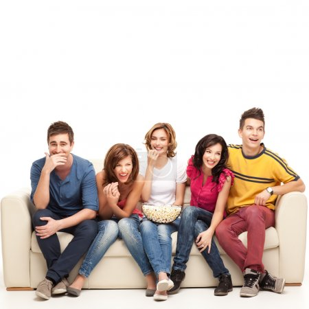 Photo for Friends sitting on couch laughing hard at comedy movie - Royalty Free Image