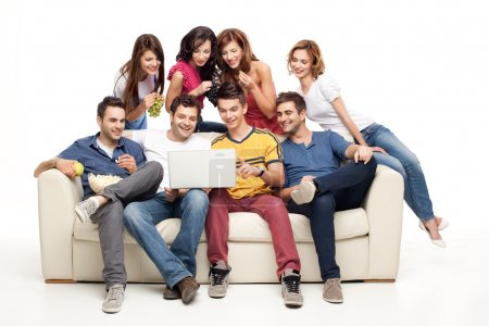 Photo for Young group of friends sitting on couch smiling at laptop - Royalty Free Image