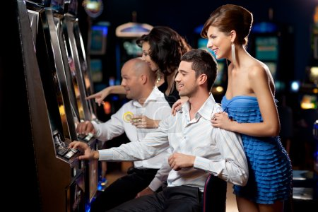 Photo for Friends enjoying playing the slot machine at the casino - Royalty Free Image