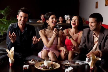 Photo for Glamourous young woman laughing, feeding ice-cream to her friend - Royalty Free Image