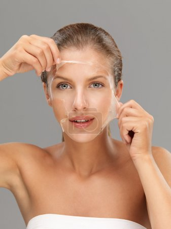 Photo for Young woman peeling off a facial mask - Royalty Free Image