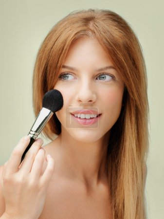 Photo for Young blonde woman applying blusher with brush - Royalty Free Image
