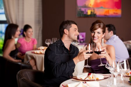 Photo for Romantic young couple at restaurant table toasting - Royalty Free Image