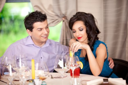Man flirting, woman annoyed at restaurant table