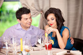 Man flirting, woman annoyed at restaurant table