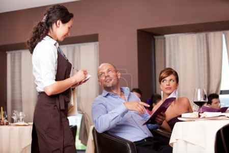 Photo for Waitress taking dinner order restaurant table young couple - Royalty Free Image