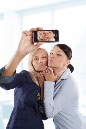 Photo for Blond and brunette office worker woman playing with a smartphone giving kisses - Royalty Free Image