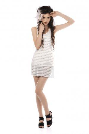 Photo pour Coup de tout le corps d'une brune enroulée modèle posant dans une robe blanche et plumes roses dans ses cheveux - image libre de droit