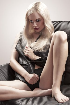 Blonde girl sitting on a black leather sofa