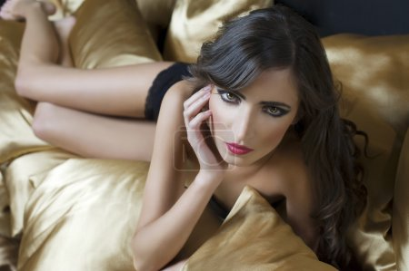 Photo for Fashion sensual shot of a girl wearing black lingerie indoor laying over yellow golden pillow with hair style - Royalty Free Image