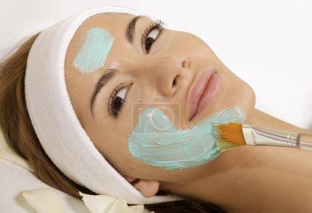 Photo pour Jeune femme à obtenir un traitement de beauté peau masque sur son visage avec brosse - image libre de droit