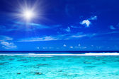 Sun over tropical ocean with vibrant colors