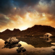Sunset over peaceful lake with boathouse in the ba...