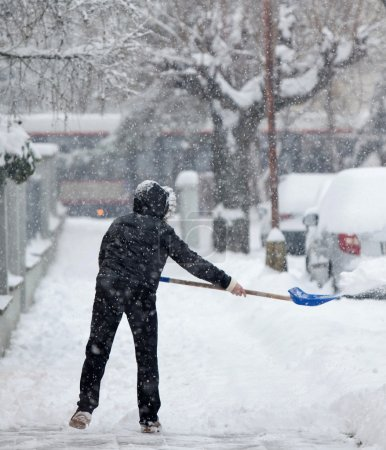 Woman shoveling snow from a sidewalk after a heavy snowfall in a