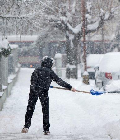Photo pour Femme pelleter la neige d'un trottoir après une lourde chute de neige dans une ville - image libre de droit