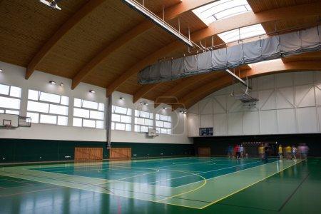 Photo pour Gymnase multifonctionnel moderne avec de jeunes se préparant pour l'entraînement - image libre de droit