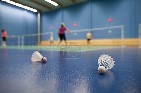 Photo pour Badminton - terrains de badminton avec les joueurs en compétition ; volants à l'avant-plan (shallow Dof ; image couleur tonifié) - image libre de droit