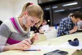 Hezká žena vysokoškolský student sedí zkoušky v učebně ful