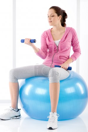 Photo for Fitness happy woman exercise dumbbell ball on white - Royalty Free Image