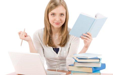 Photo pour Étudiant adolescent femme écrire devoirs avec ordinateur portable livre - image libre de droit