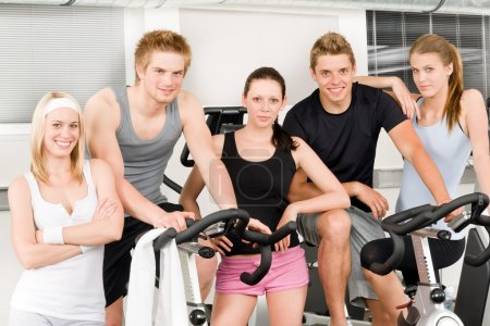 Fitness young group at gym bicycle