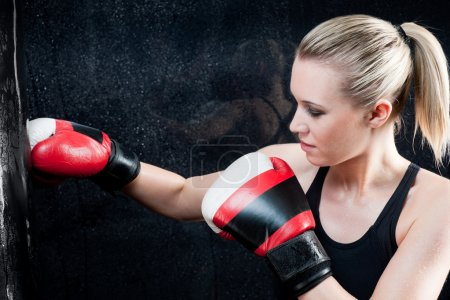 Photo pour Femme d'entraînement de boxe avec sac de boxe à porter des gants de gym - image libre de droit