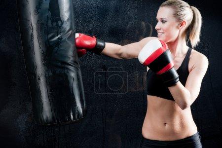 Photo pour Femme d'entraînement de boxe avec sac de boxe en gants de sport - image libre de droit