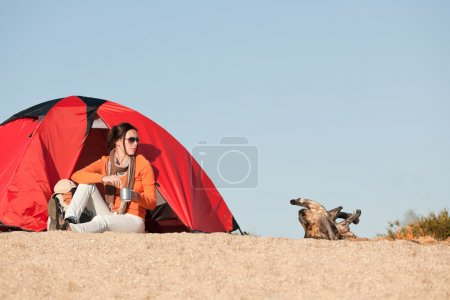 Camping happy woman sitting outside beach tent