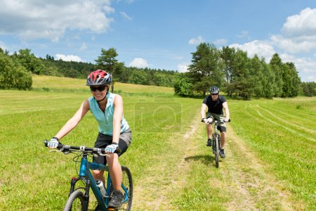 Sport couple riding mountain bicycles in coutryside